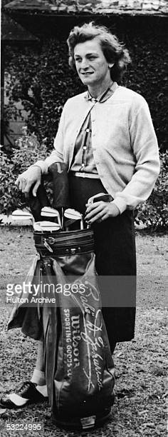 Legendary American athlete Babe Didrikson Zaharias stands on a field with a set of golf clubs with her name engraved on the bag late 1940s Zaharias...