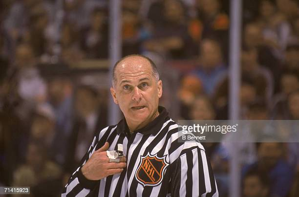 Legendary Canadian ice hockey linesman Ray Scapinello gestures at himself as he speaks on the ice and officiates a game at Continental Airlines...