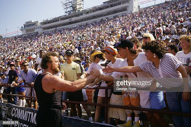 Legendary defensive end John Matuszak of the Los Angeles Raiders signs autographs for fans during the game against the Detroit Lions at the Los...