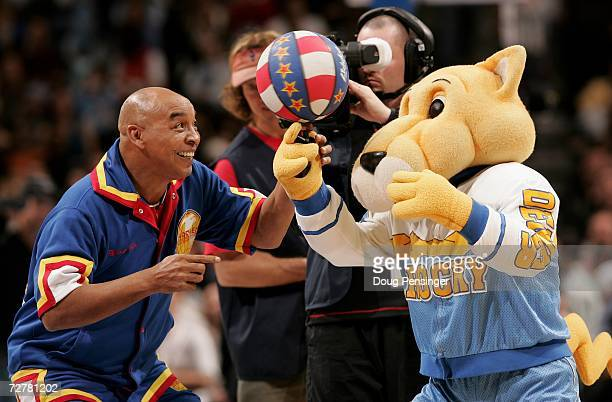 Legendary Harlem Globetrotter Curly Neal helps Denver Nuggets mascot Rocky spin a basketball during a game against the Miami Heat on December 8 2006...