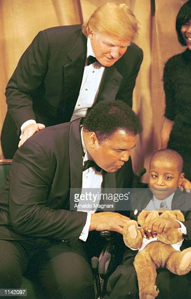 Legendary heavyweight boxing champ Muhammad Ali holds a UCP bear and kisses Yasin Shelton a cerebal palsy patient as Donald Trump looks on March 14...