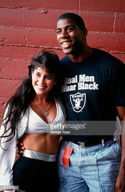 Legendary Los Angeles Laker basketball player Earvin 'Magic' Johnson poses with a Raiderette cheerleader at a 1990 Los Angeles California Raider...