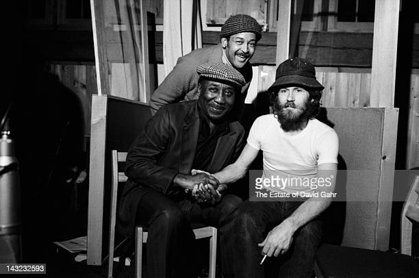 Legendary record producer Henry Glover blues guitarist and singer Muddy Waters and musician and founding member of The Band Levon Helm pose for a...