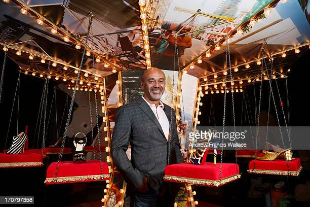 Legendary shoe designer Christian Louboutin poses with some of his famous footwear while preparing for an exhibition of his work at the Design...