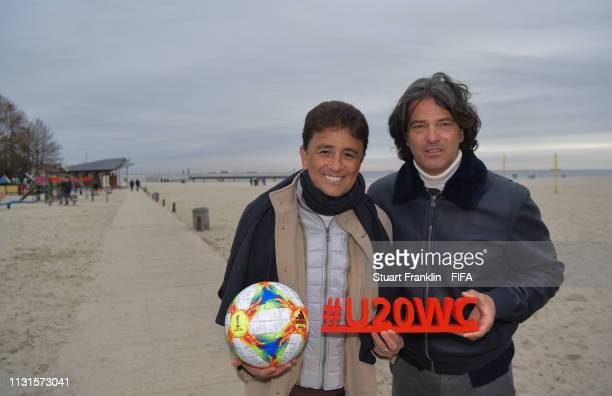 Legends Bebeto of Brazil and Fernando Couto of Portugal pose with the official FIFA U20 World Cup match ball and hashtag on the beach prior to the...