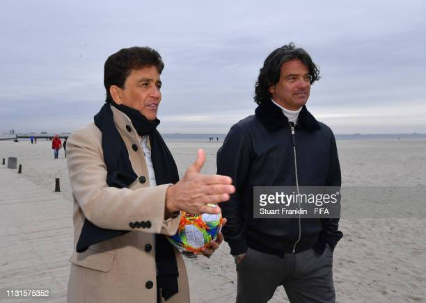 Legends Bebeto of Brazil and Fernando Couto of Portugal walk with the official FIFA U20 World Cup match ball on the beach prior to the official draw...