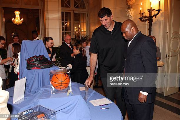 Legends Jared Jackson and George Muresan look at memorabilia during the Sudan Sunrise Benefit at the Meridian International Center on May 12 2011 in...