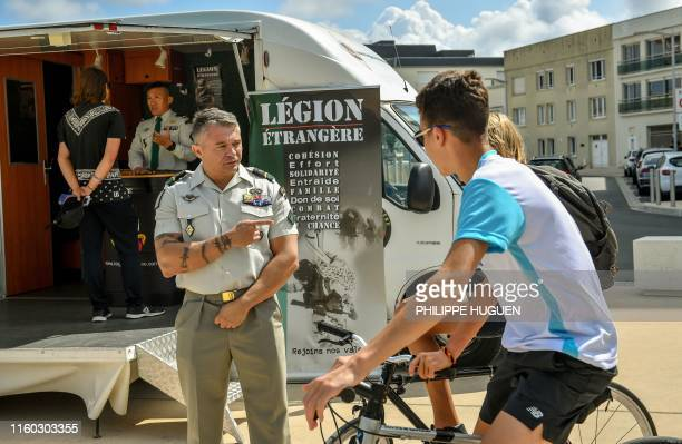 A Legion NCO talks to young people on 7 August 2019 in BercksurMer as part of a recruitment campaign for the Foreign Legion