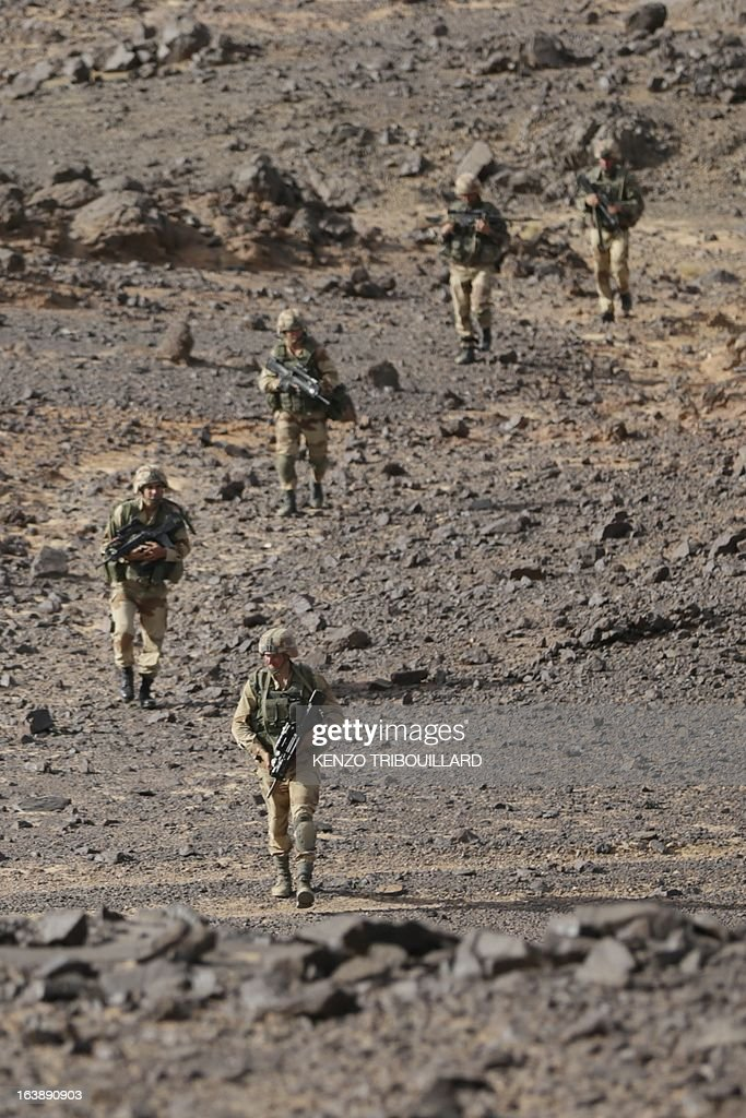 Legionnaires of the French army's 2nd Foreign Parachute Regiment walk during an operation in the Adrar of the Ifoghas mountains on March 17, 2013.A French corporal was killed tracking down jihadist fighters in their northern Mali mountain bastions, bringing to five the number of French deaths since Paris launched a military offensive in the country two months ago. Defence Minister Jean-Yves Le Drian said on March 17, 2013 the 24-year-old soldier was killed and three of his comrades wounded when their vehicle was struck by a roadside bomb blast in the Ifoghas mountains, without saying when it happened.