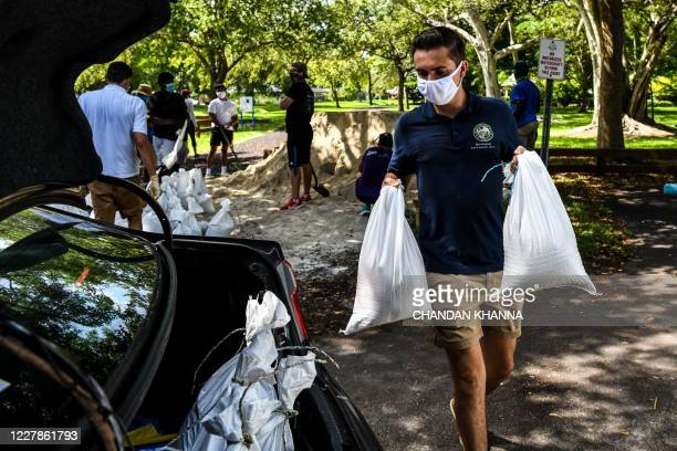 Legislative Assistant Ryan Fernandez, puts sand bags in a resident's car trunk in Palmetto Bay near Miami, on July 31, 2020 as Floridians prepare for...