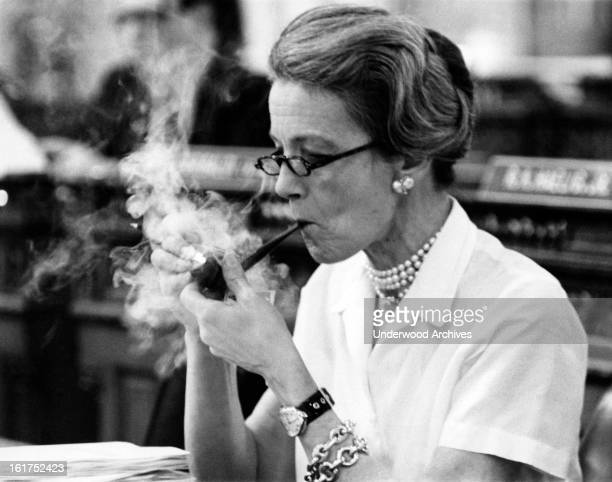 Legislator Millicent Fernwick lights up her pipe at her desk in the State Assembly, Trenton, New Jersey, April 15, 1970. She is pushing for the New...