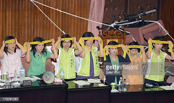 Legislators from Taiwan's main opposition Democratic Progressive Party wear head banners before a vote is taken on whether to build a fourth nuclear...
