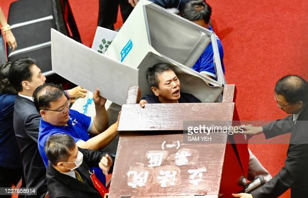 Legislators from Taiwans main opposition Kuomintang take away a polling booth as they protest against Taiwan President Tsai Ing-wen's nomination of...