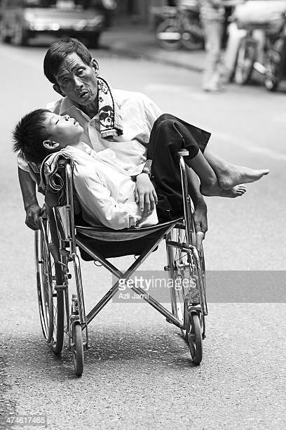 CONTENT] A legless man on a wheelchair with a boy lying sleeping on his lap