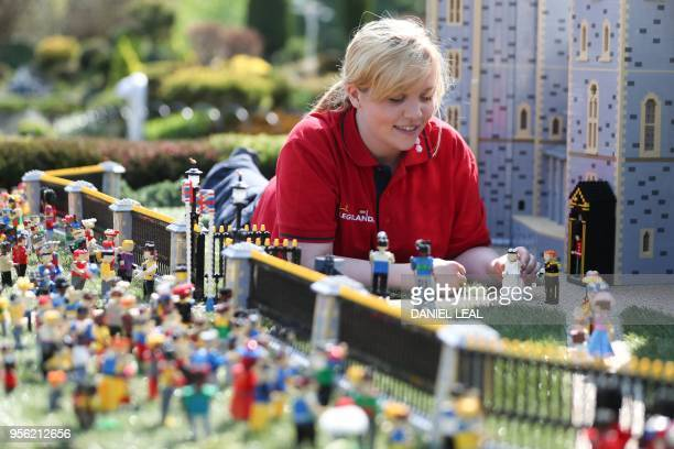 Legoland employee Lucy poses putting a Lego model of US actress Meghan Markle in place next to her husbandtobe Britain's Prince Harry outside a...