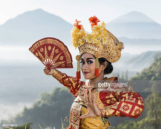 legong dancer infront of distant volcano