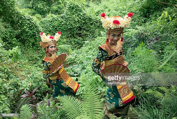 Legong dancers in traditional costume walking in rainforest