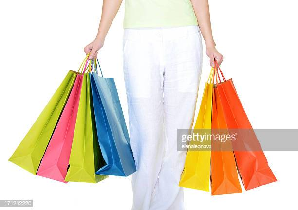 Legs and arms of woman holding colorful shopping bags