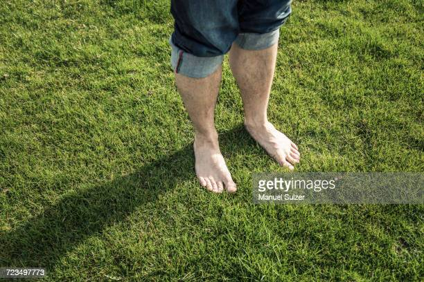 Legs and bare feet of man standing on green grass
