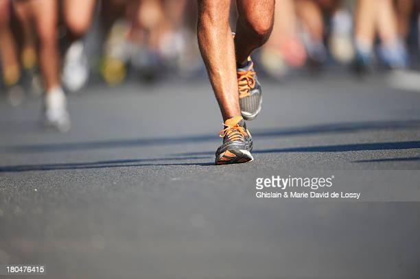 legs and feet of joggers, running a marathon - maratona foto e immagini stock