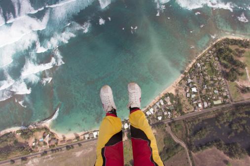 Legs and feet of skydiver above coastline - gettyimageskorea