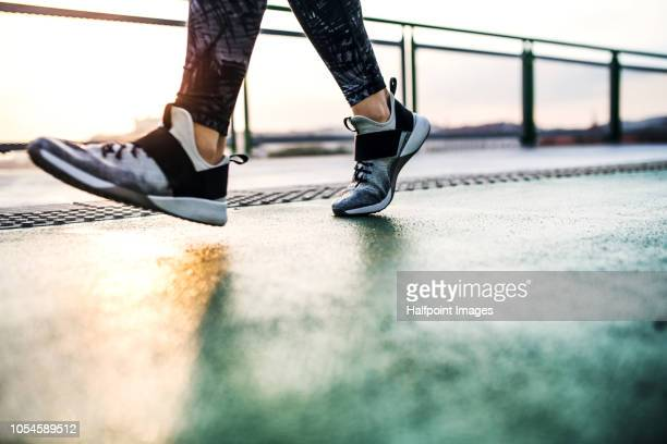 Legs and feet of unrecognizable woman running outdoors on a bridge in the city.