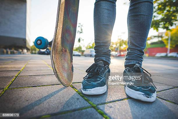 legs and feet of young male urban skateboarder standing on sidewalk - enge jeans stock-fotos und bilder