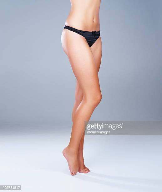 Legs and mid-section of woman wearing black panties