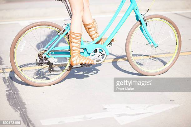 legs and strappy sandals of young female cyclist at venice beach, los angeles, california, usa - strap stock pictures, royalty-free photos & images