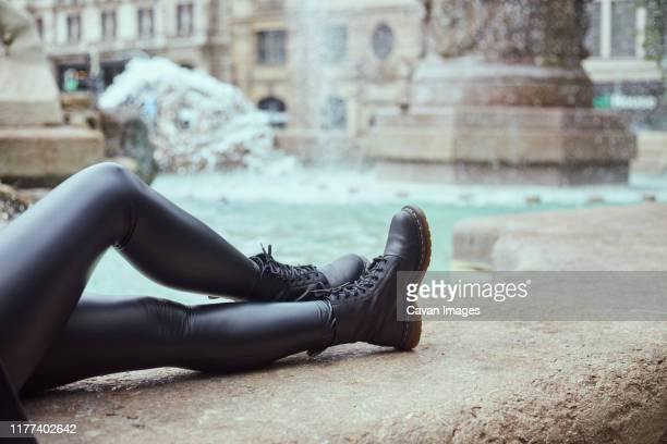 legs crossed on the wall by fountain - leather boot stock pictures, royalty-free photos & images