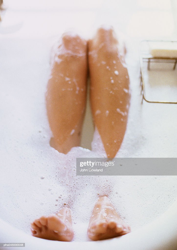 Legs in bathtub surrounded by foam, close-up : Stock Photo