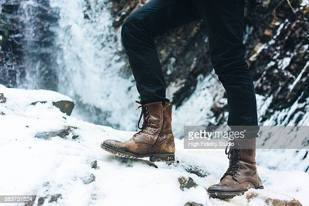 legs in boots on the background of waterfall in winter - leather boot stock pictures, royalty-free photos & images