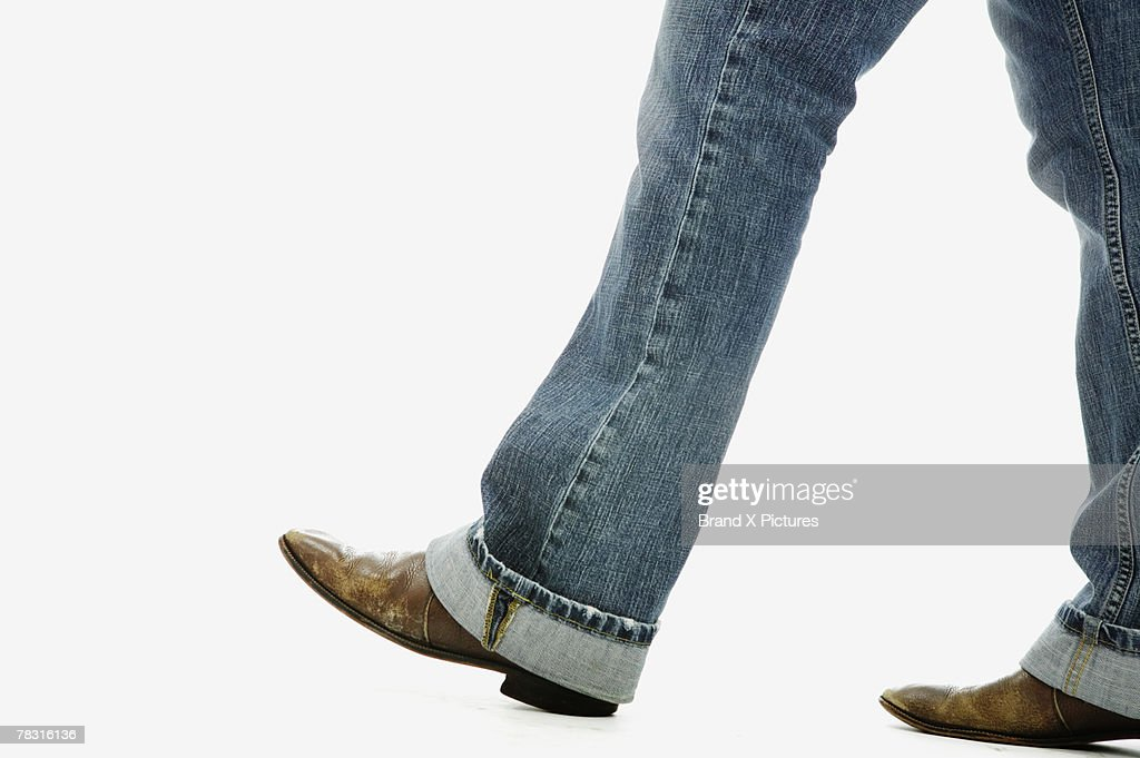 Legs in jeans and boots : Stock Photo