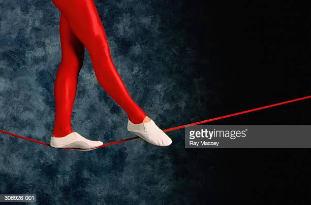 Legs in red leggings balancing on  tightrope, grey background