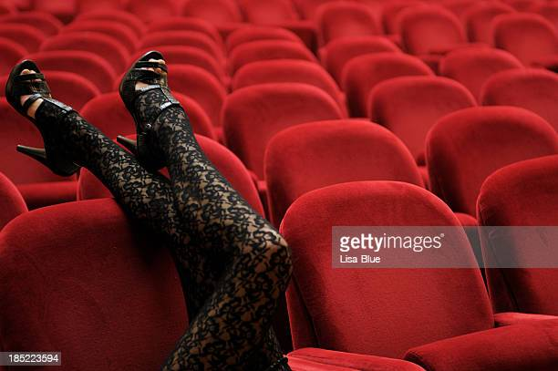 legs leaning on theater chair - nylon feet stock photos and pictures