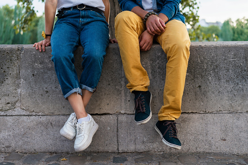 Legs of a couple sitting on a wall - gettyimageskorea