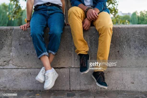 legs of a couple sitting on a wall - trousers stock pictures, royalty-free photos & images