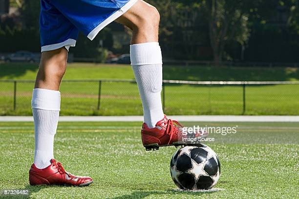 Legs of a footballer and football