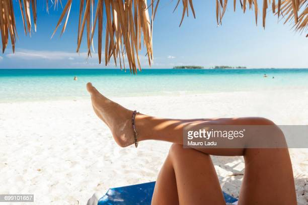 legs of a girl under the shadow of some palm trees hut on a beautiful beach in cayo guillermo, cuba - anklet stock pictures, royalty-free photos & images
