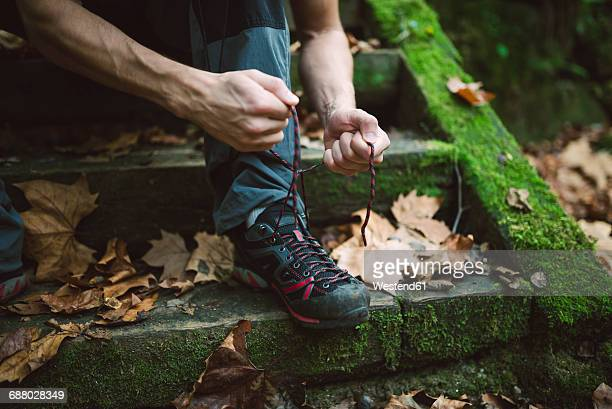 Legs of a hiker sitting on stairs lacing his shoes