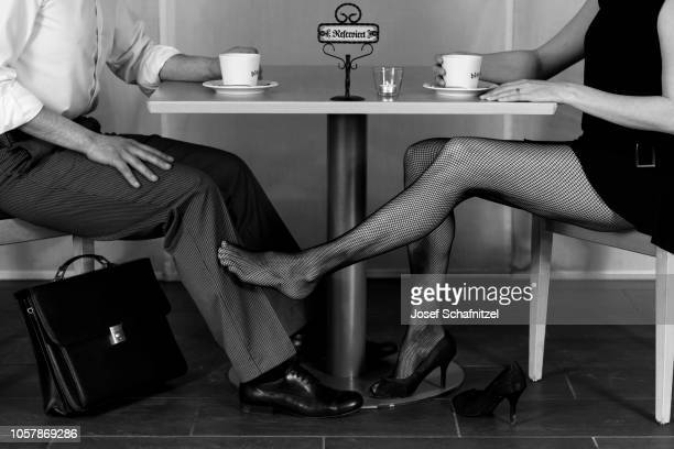 Legs Of A Man Businessman And Woman With Fishnets Under Table