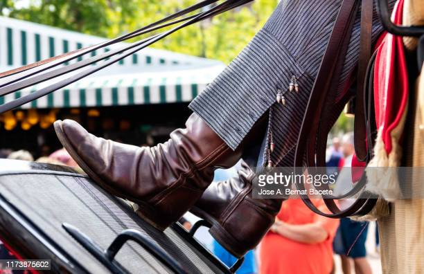 legs of a man in traditional boots driving a horse carriage in albacete fair, spain, - ブーツイン ストックフォトと画像