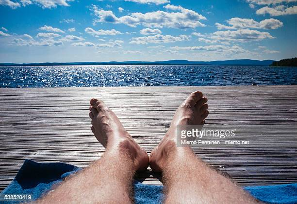 legs of a man sunbathing on a wooden pier - hairy legs stock photos and pictures