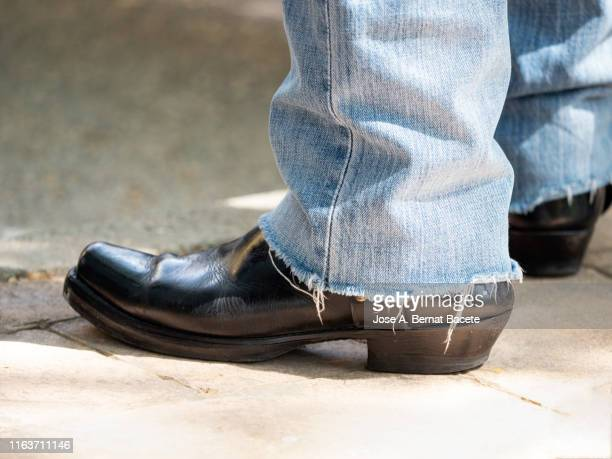 legs of a man with black leather boots and jeans. - ブーツイン ストックフォトと画像