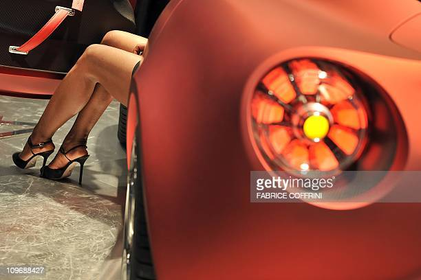 Legs of a model are seen next to an Alfa Romeo 4C GTA concept car wait at the Italian car maker's booth during the Geneva car show on March 1 2011 in...