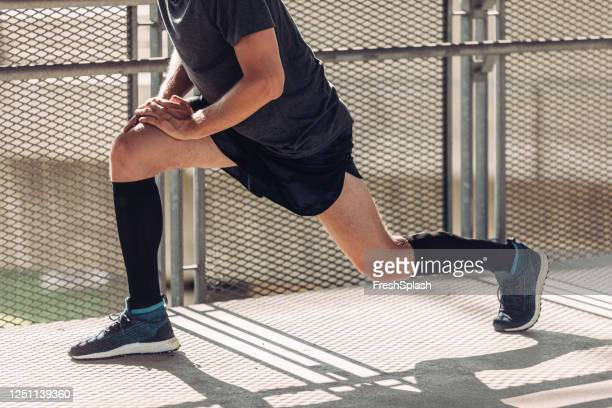 legs of a runner stretching to warm up - men wearing stockings stock pictures, royalty-free photos & images