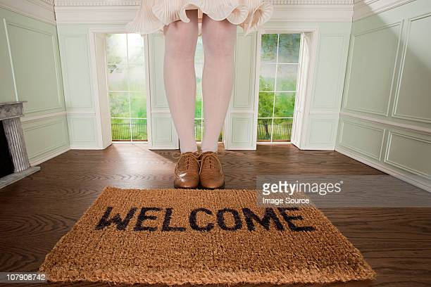 legs of a woman and welcome mat in small room - big foot stock photos and pictures