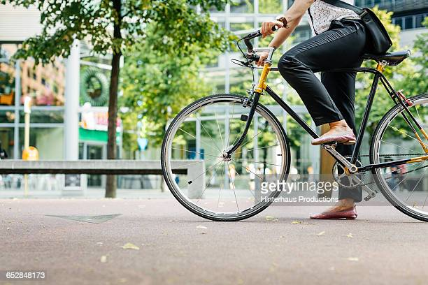 legs of a young businesswoman on a bicycle - fietsen stockfoto's en -beelden