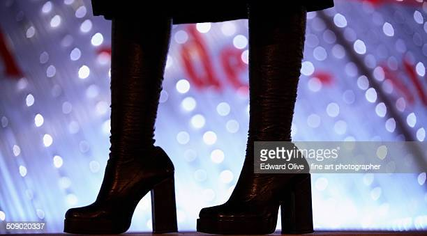 Legs of a young lady in high heel leather boots