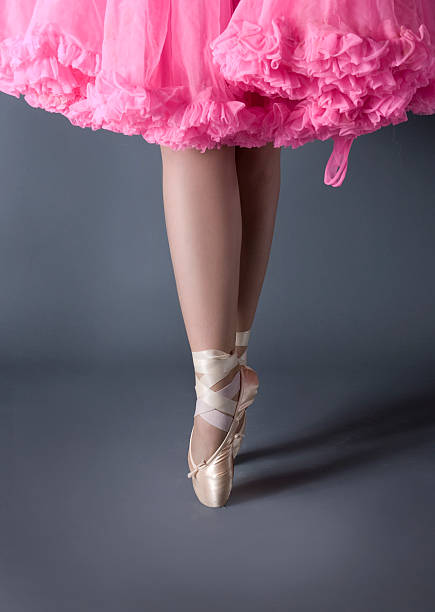 legs of ballet dancer on point with pink tutu